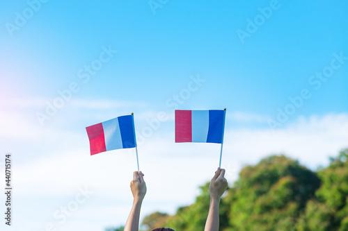Fototapeta hand holding France flag on blue sky background