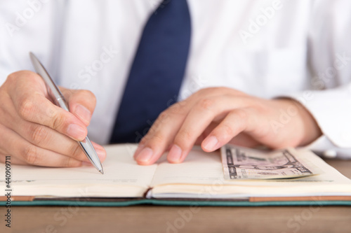 Fotografiet Man jot down things and some dollar banknotes in his notebook