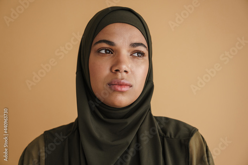 Fototapeta Black muslim woman in hijab posing and looking aside