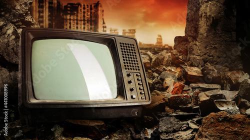 Photo Photo of old fashioned tv set laying on pile of bricks on ruined city wasteland background