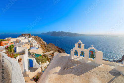 Foto Stunning cupolas with the Caldera (volcano) in the distance in the Greek island