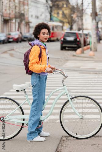 Young african american woman standing near bike on road on urban street Fototapet