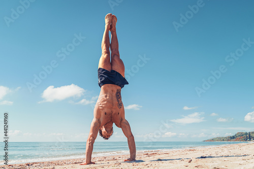 Fototapeta Muscular bodybuilder fitness man with a naked torso stands on arm on the beach