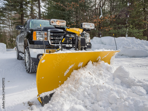 Photo Pickup truck plowing snow off driveway