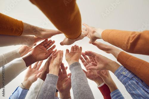 Slika na platnu Closeup diverse colleagues joining hands giving high five bottom view