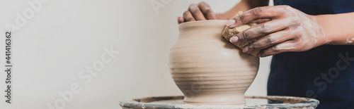 Fotografija partial view of young african american woman modeling wet clay pot on wheel with