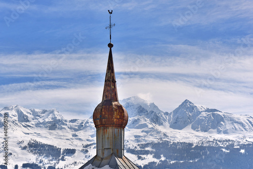 Canvas metal bell tower of a church in the shape of a bulb on a snowy mountain backgrou