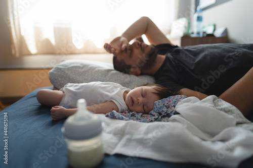 Fotografie, Obraz Exhausted man father lying by his three months old baby on the bed at home sleep