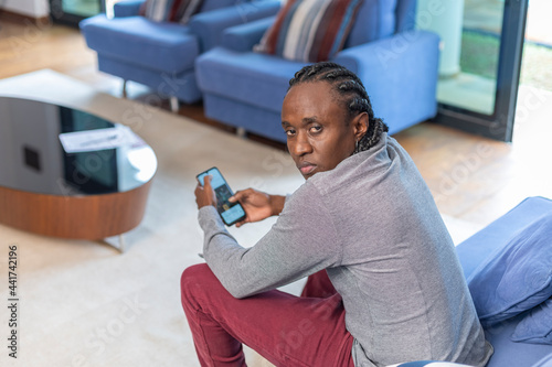 Murais de parede African descendant working on the couch with her cell phone, looking at camera with serious expression