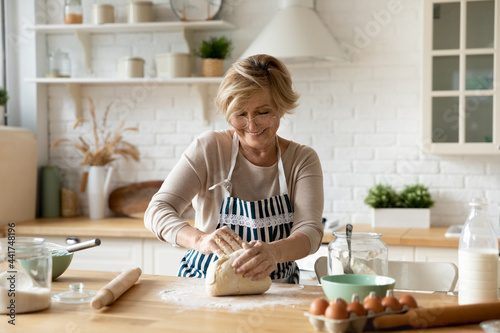 Happy beautiful older middle aged retired woman in eyeglasses wearing apron kneading dough, involved in preparing homemade pastry alone in modern kitchen, domestic culinary cooking activity concept Fototapeta