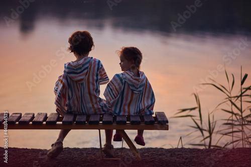 Billede på lærred cute children, siblings sitting on the bench by the lake at warm summer evening