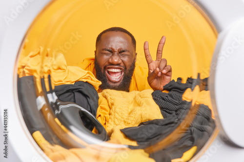 Obraz na plátně Glad dark skinned bearded man does laundry poses against pile of clothes with detergent in washing machine drum makes peace gesture busy with domestic duties