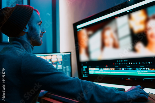 Foto Attractive Male Video Editor Works with Footage or Video on His Personal Computer, he Works in Creative Office Studio or home