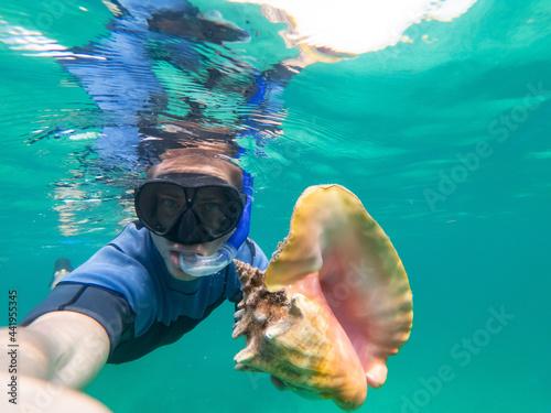 Slika na platnu Caucasian man holding and huge conch shell during snorkeling underwater