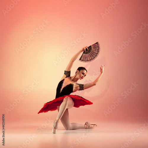 Canvas Print Young and incredibly beautiful ballerina is posing and dancing at red studio full of light