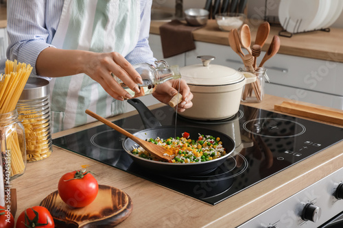 Fotografija Woman cooking tasty rice with vegetables on stove in kitchen, closeup