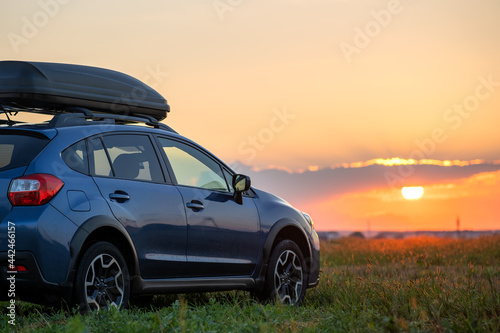 SUV car with roof rack luggage container for off road travelling parked at roadside at sunset. Road trip and getaway concept.