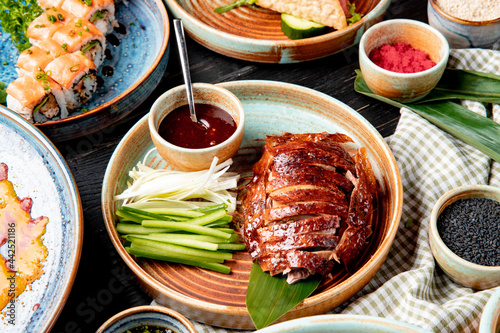 Fotografia side view of traditional asian food peking duck with cucumbers and sauce on a pl