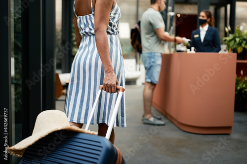 Unrecognizable female guest with travel bag arriving to hotel during COVID-19 pandemic Fototapet