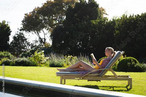 Fotografie, Obraz Smiling caucasian woman relaxing on sun lounger in beautiful sunny garden readin