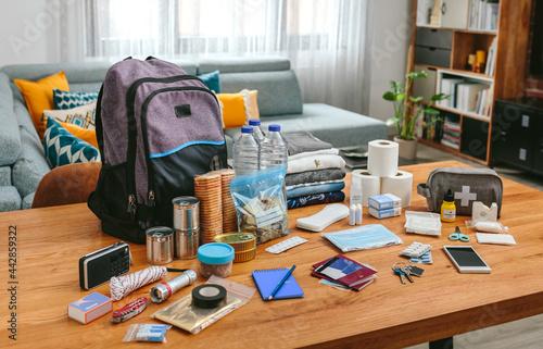 Fototapeta Emergency backpack equipment organized on the table in the living room