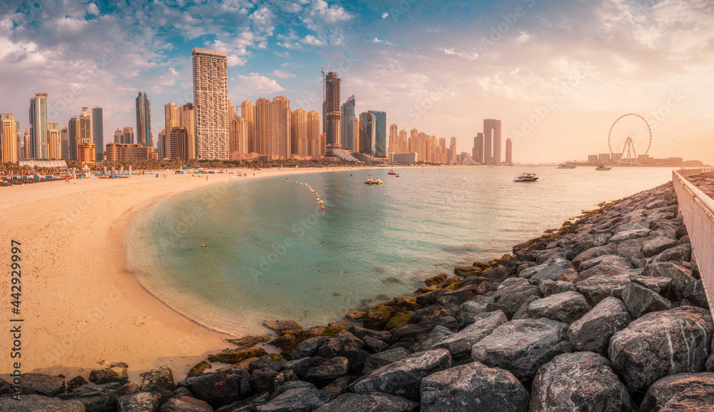 Panoramic view of the golden sand illuminated by the setting sun in the JBR beach area. Amazing skyscrapers and warm waters of the Persian Gulf are waiting for guests and tourists