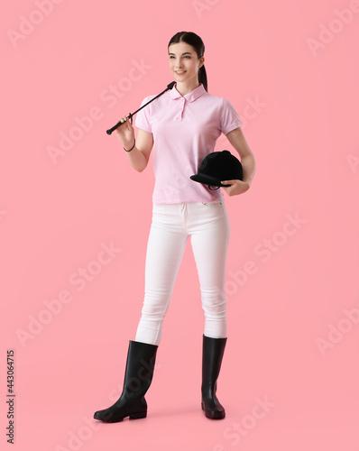 Beautiful female jockey on color background Fototapeta