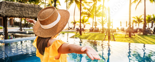 Fotografie, Obraz Young woman traveler relaxing and enjoying the sunset by a tropical resort pool