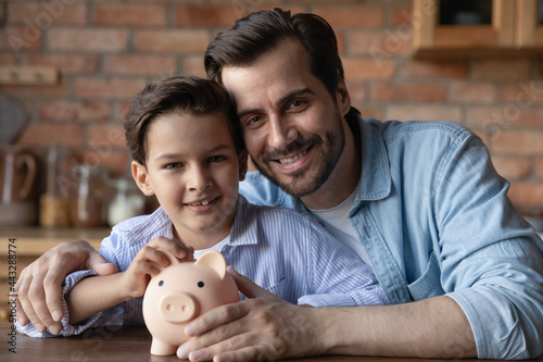 Murais de parede Happy dad and little son holding piggy bank, smiling, looking at camera