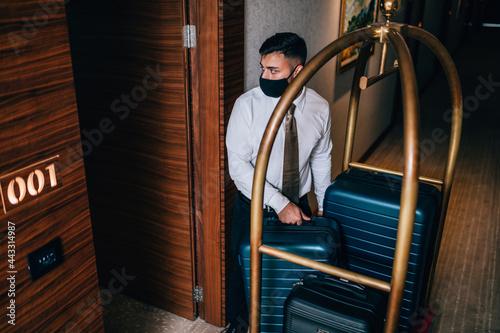 Canvastavla Bellboy with luggage cart in hotel hallway