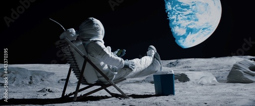Fotografering Back view of lunar astronaut opens a beer bottle while resting in a beach chair