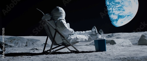 Fotografie, Obraz Back view of lunar astronaut opens a beer bottle while resting in a beach chair