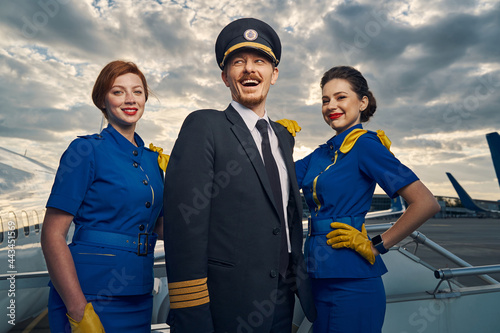 Cheerful aviator and flight attendants standing on the boarding stairs Fototapeta