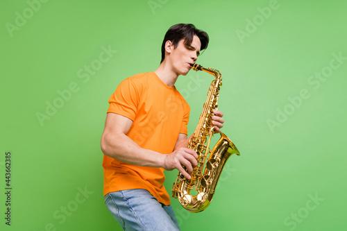 Wallpaper Mural Photo of joyful happy young man artist play saxophone good mood wear jeans isola