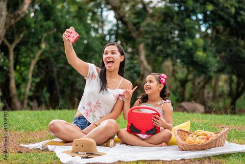 Slika na platnu Madre e hija muy felices tomando un selfie con el celular en un día de campo