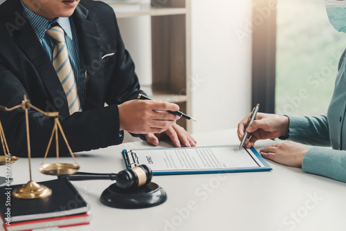 Photo Close-up of a businessman hand pointing at a document to a client holding a pen to sign contract documents at the office