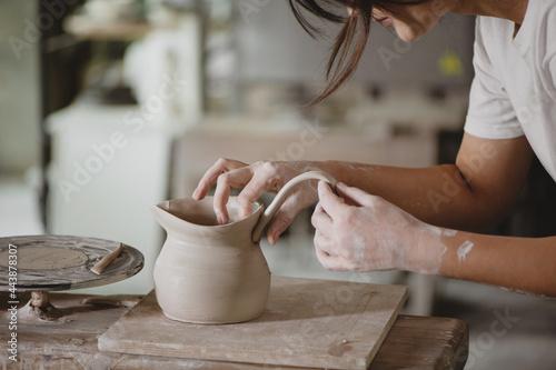 Slika na platnu Young woman making pottery in studio.