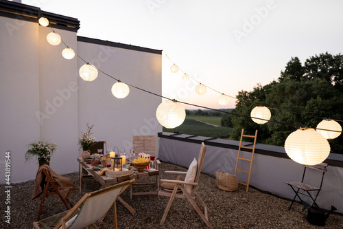 Canvas Print Beautifully decorated roof terrace in natural boho style with a dining table full of food at summer time