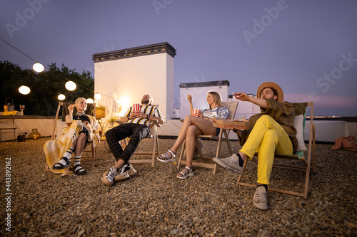 Fotografie, Obraz Young people watching football match or some film with popcorn outdoors on a rooftop terrace at night