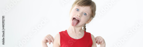 Fotografia Little girl in red dress showing tongue