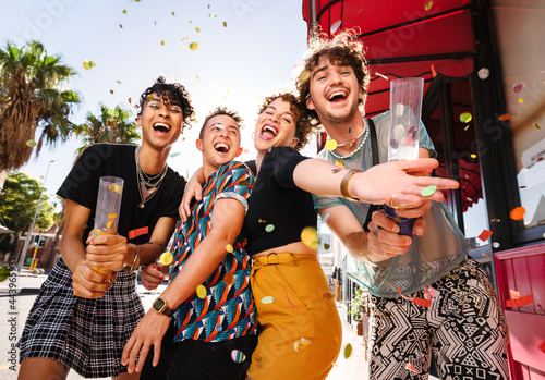 Joyful group of friends celebrating with confetti