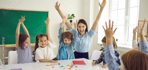 Obraz na plátně Happy children and educator raising hands up sitting at table in modern classroom