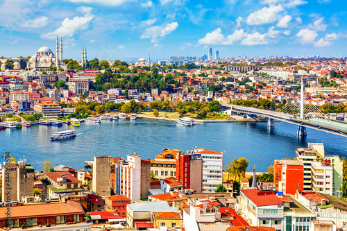 Touristic sightseeing ships in Golden Horn bay of Istanbul and mosque with Sultanahmet district against blue sky and clouds Fototapet