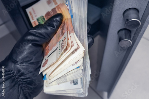 Fotografia Robber's black-gloved hand pulls out wad of Russian rubles money from safe