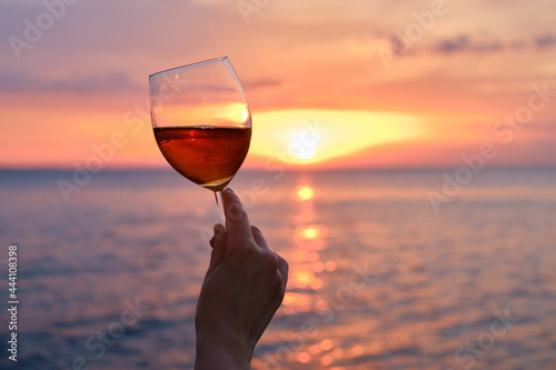 Canvas A glass of red wine in the hands of a girl in the rays of the sunset on the seashore