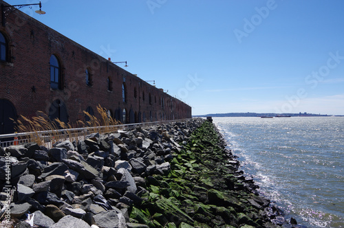 Photo Brick Warehouse On Rocky Waters Edge In Red Hook Brooklyn On A Bright Cold Day