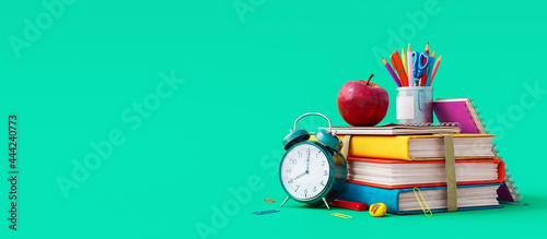 Photographie School accessories with apple, books and alarm clock on green background