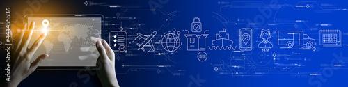 Fotografie, Obraz Businesswoman hand using Digital tablet computer of global logistics network distribution and transportation Ui, Smart logistics, Innovation future of transport on blue background