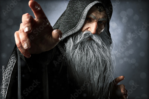 Canvas Print Portrait closeup of a wise Warlock old hooded wizard posing ready to cast an enchanted powerful spell  with a blue gradient background