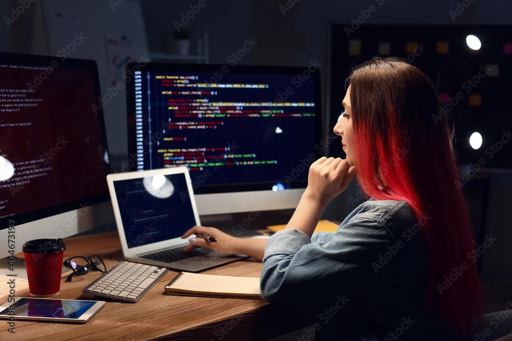 Leinwandbild Motiv - Pixel-Shot : Female programmer working with laptop in office at night